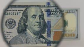 Unter Verwendung einer Lupe hundert Dollarschein sich nähern stock video