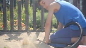 Unter Verwendung einer Pumpe modellierte ein neugieriges Kind eine Vulkaneruption in einem Sandkasten stock footage