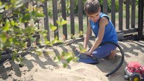 Unter Verwendung einer Pumpe modellierte ein neugieriges Kind eine Vulkaneruption in einem Sandkasten stock video