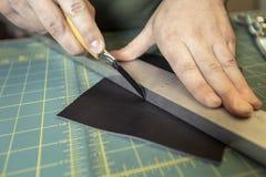 Unter Verwendung eines geraden Blattes, zum des Leders zu schneiden lizenzfreies stockfoto