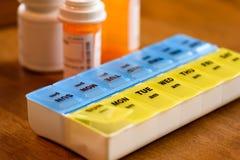 Unter Verwendung eines Pillenhalters als tägliche Anzeige für das Nehmen der Medizin Lizenzfreie Stockbilder