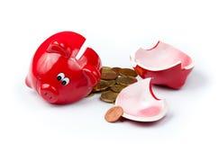 Unterbrochene piggy Querneigung mit Münzen auf Weiß Lizenzfreie Stockfotografie