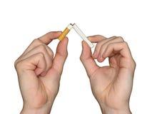 Unterbrochene Zigarette in den Händen Stockfotos