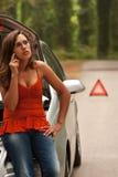 Unterbrochenes Auto - junge Frauen-Aufrufe für Unterstützung lizenzfreie stockfotografie