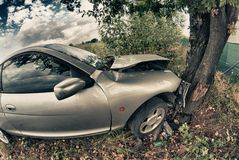 Unterbrochenes Auto nach einem Unfall gegen einen Baum Stockbilder