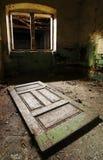 Unterbrochenes Fenster und alte Tür auf dem Fußboden Stockfotografie