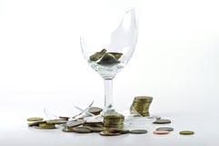 Unterbrochenes Glas und Münze Stockfoto