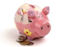 Unterbrochenes Piggybank und Münzen Stockfoto