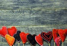 Untere Rahmengrenze von bunten Herzen des handgemachten Filzes auf dunklem altem hölzernem Hintergrund Stockfotografie