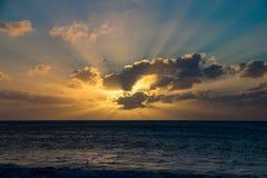 Untergehende Sonne, die sich noch über einem ruhigen Ozean reflektiert lizenzfreie stockbilder