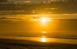 Untergehende Sonne int, den er am Erholungsort auf den Strand setzt stockbild