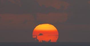 Untergehende Sonne mit Wolken Stockfoto
