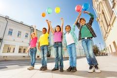 Unterhalb der Ansicht von multinationalen Kindern mit Ballonen Lizenzfreie Stockbilder
