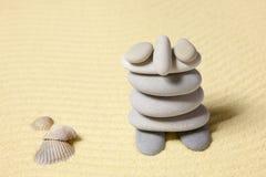 Unterhaltende Abbildung des Mannes vom Kiesel auf Sand Stockfotos