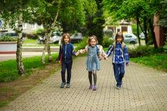 Unterhaltende kleine Schüler gehen zur Schule, die Händen angeschlossen wird Stockfotos