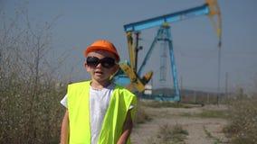 Unterhaltender kleiner Kinderarbeiter mit einem Sturzhelm und Weste nahe Treibstoffölpumpe stock video