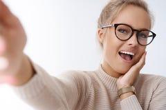 Unterhaltener und glücklicher zarter attraktiver Kaukasier weiblich mit angemessener Haaruhr und -gläsern, die unverschämtes glüc lizenzfreies stockbild