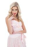 Unterhaltenes blondes Modell im rosa Kleid, das einen Finger auf dem Mund aufwirft Stockbild