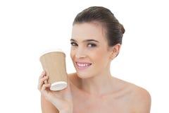 Unterhaltenes natürliches braunes behaartes Modell, das einen Tasse Kaffee hält Lizenzfreie Stockfotos