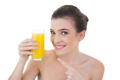Unterhaltenes natürliches braunes behaartes Modell, das ihr Glas Orangensaft zeigt Lizenzfreie Stockfotos