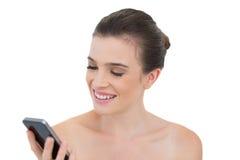 Unterhaltenes natürliches braunes behaartes Modell, das ihren Handy betrachtet Stockbild