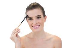 Unterhaltenes natürliches braunes behaartes Modell unter Verwendung einer Augenbrauenbürste Stockbilder