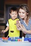 Unterhaltsame Kindheit, ein kleiner Junge, der mit seiner Mutter spielt, zeichnet, Farben auf den Palmen stockfoto