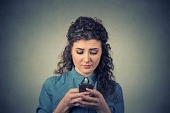 Unterhaltungsc$simsen der umgekippten traurigen unglücklichen ernsten Frau am Telefon Stockfotografie