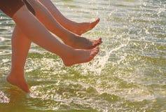 Unterhaltungsfüße eines jungen Paares im Wasser an einem sonnigen Tag Stockfoto