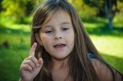 Unterhaltungsgestenhand des kleinen ernsten Mädchens oben Stockfoto
