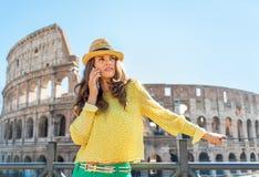 Unterhaltungshandy der Frau vor colosseum Stockfotografie