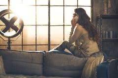Unterhaltungshandy der jungen Frau in der Dachbodenwohnung stockfoto