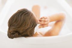 Unterhaltungshandy der jungen Frau während in der Badewanne. hintere Ansicht Lizenzfreies Stockbild