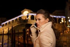 Unterhaltungsmobiltelefon der Frau beim Verbringen von Weihnachtszeit in Venedig Lizenzfreie Stockfotos