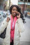 Unterhaltungsmobiltelefon der Schwarzafrikaner-Amerikanerin in der Stadt Lizenzfreie Stockfotografie
