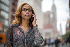 Unterhaltungsmobiltelefon Latina-Frau in der Stadt Stockfoto