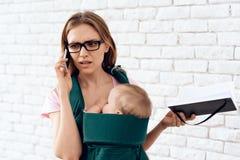 Unterhaltungstelefon der Geschäftsfrau und neugeboren halten lizenzfreie stockfotografie