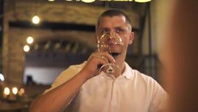 Unterhaltungstoast des gut aussehenden Mannes mit Rotweinglas am romantischen Abendessen für zwei im Restaurant Paare in trinkend stock video