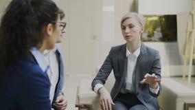 Unterhaltungsund duscussing Terminkontrakt der Geschäftsfrau mit den Teilhabern, die auf Couch in der modernen Büromitte sitzen