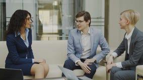Unterhaltungsund duscussing Terminkontrakt des Geschäftsmannes mit den weiblichen Teilhabern, die auf Couch im Konferenzzimmer si stock video