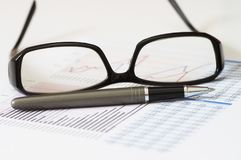Unternehmensanalyse und Bericht mit Stift, Gläsern und Diagramm Stockfotos