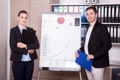 Unternehmensarbeitskräfte in einem Büro nahe bei einer Flip-Chart stockfoto