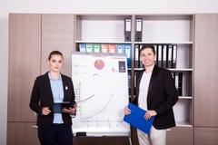 Unternehmensarbeitskräfte in einem Büro nahe bei einer Flip-Chart stockfotos