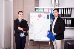 Unternehmensarbeitskräfte in einem Büro nahe bei einer Flip-Chart lizenzfreies stockfoto