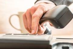 Unternehmensberater, der heraus an einem Festnetztelefontelefon wählt Lizenzfreies Stockfoto