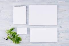 Unternehmensidentitä5sschablone, Briefpapier mit grünem Laub auf weichem hellblauem hölzernem Brett lizenzfreie stockbilder