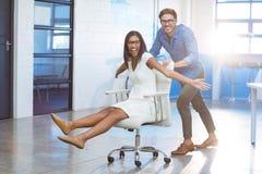 Unternehmensleiter, der Geschäftsfrau im Bürostuhl drückt stockbild
