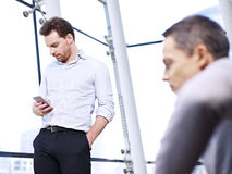 Unternehmensleiter, der Handy im Büro verwendet Lizenzfreie Stockbilder