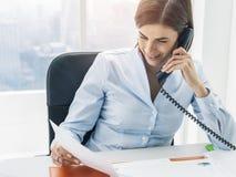 Unternehmensleiter, der im Büro arbeitet und Telefonanrufe macht stockbild