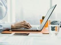 Unternehmensleiter, der mit einem Laptop arbeitet und online anschlie?t stockfoto